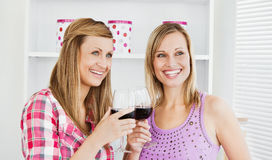Happy female friends drinking wine in the kitchen Stock Photos