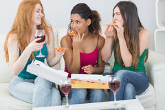 Happy female friends eating pizza with wine at home Stock Photo