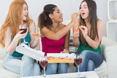 Happy female friends eating pizza with wine at home Stock Images