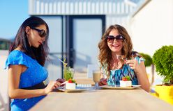 Happy female friends enjoying cakes in cafe, pregnant women Royalty Free Stock Photos