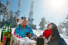 Happy female friends enjoying hot drink in cafe at ski resort. Together Royalty Free Stock Image