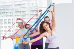 Happy female friends exercising with resistance bands Stock Image