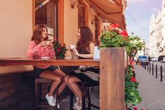 Happy female friends having coffee in outdoor cafe in summer. Women chatting and chilling stock photography