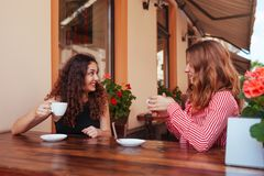 Happy female friends having coffee in outdoor cafe in summer. Women chatting and chilling while having drinks on street royalty free stock photos