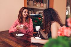 Happy female friends having coffee in outdoor cafe in summer. Women chatting and chilling while having drinks on street royalty free stock photo