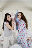 Happy female friends having pillow fight Stock Images