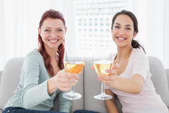 Happy female friends holding out wine glasses at home Stock Photos