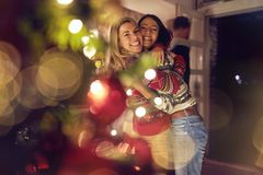 Female friends hugging and celebrating Christmas royalty free stock photos