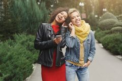 Happy female friends listen to music outdoors royalty free stock photography