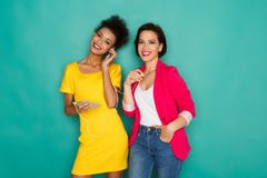 Happy female friends listen to music at studio background Royalty Free Stock Photo