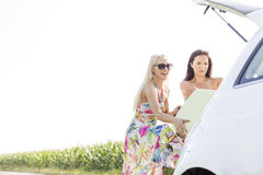 Happy female friends loading luggage in car trunk against clear sky Royalty Free Stock Image