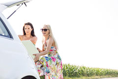 Happy female friends loading luggage in car trunk against clear sky Stock Photo