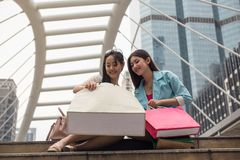 Happy female friends look at shopping bags Stock Photos