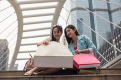 Happy female friends look at shopping bags. Happy female friends look at luxury fashion fabric in shopping bag. Two beautiful young Asian women shop in modern Stock Photos