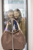 Happy female friends looking at purse through display window Royalty Free Stock Images