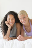 Happy Female Friends Lying In Bed Stock Images
