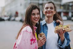 Happy female friends making photo with hot dogs royalty free stock photo