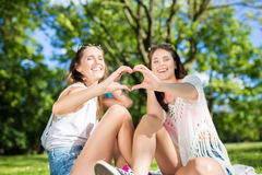 Happy female friends outside making heart sign. Portrait of happy female friends outside making heart sign royalty free stock images