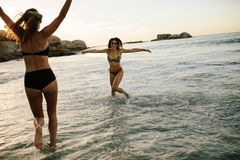 Happy female friends playing at beach Royalty Free Stock Images