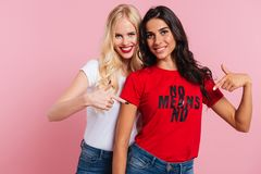 Happy female friends pointing at shirt with phrase and smiling isolated. Happy beautiful female friends in casual pointing at shirt with phrase and smiling royalty free stock photos