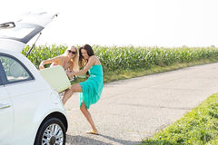 Happy female friends pushing luggage in car trunk against clear sky Royalty Free Stock Photography
