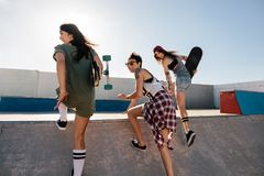 Happy female friends running over skateboard ramp. Group of female skaters enjoying at skate park Royalty Free Stock Photography