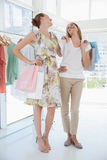 Happy female friends with shopping bags at clothing store Stock Photo