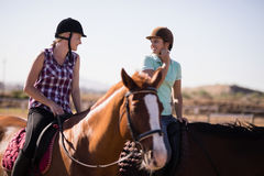 Happy female friends talking while horseback riding. On field at paddock stock image