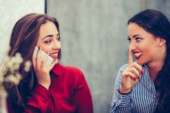 Happy female friends talking on phone and showing silence gesture while looking each other. Sitting in the table in a cafe stock images