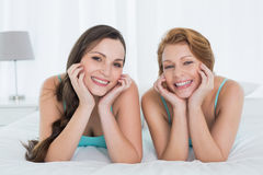 Happy female friends in teal tank tops lying in bed Stock Photography
