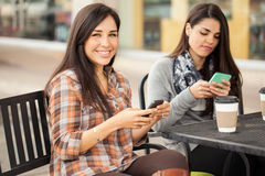 Happy female friends using a mobile phone. Cute young Hispanic brunette using her smartphone and smiling while having coffee with some friends Royalty Free Stock Photos
