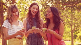 Happy female friends using their smartphones and laughing