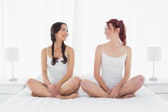 Happy female friends in white tank tops sitting on bed Stock Photo