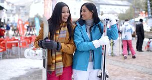 Happy female friends at a winter ski resort. Happy attractive stylish female friends at a winter ski resort standing side by side chatting and holding their stock video