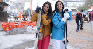 Happy female friends at a winter ski resort Stock Photos