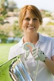 Happy Female Golfer Holding Trophy Stock Photo
