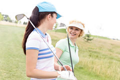 Happy female golfers talking at golf course Stock Images
