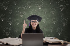 Happy female graduate has idea on lamps drawing background Royalty Free Stock Images