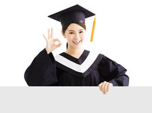 Happy female graduate showing   blank board with ok gesture Stock Photos