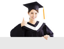 Happy female graduate showing   blank board with thumb up Royalty Free Stock Photography