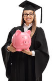 Happy female graduate student with a piggybank Royalty Free Stock Images