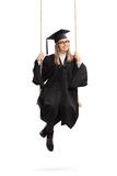 Happy female graduate student on a swing Royalty Free Stock Images