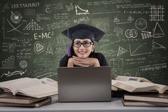 Happy female graduate thinking using laptop at class Stock Photography