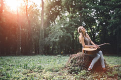 Happy female guitar player. Enjoying freedom in nature Stock Photography