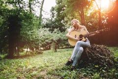 Happy female guitar player Stock Photos