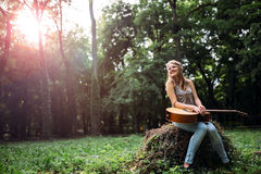 Happy female guitar player. Enjoying freedom in nature Royalty Free Stock Image