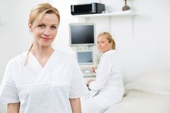 Happy Female Gynecologist With Colleague In. Portrait of happy female gynecologist with colleague using ultrasound machine in background at clinic stock images