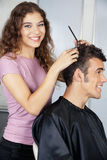 Happy Female Hairdresser Cutting Client's Hair Stock Image