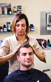 Happy female hairstylist setting client's hair Royalty Free Stock Photo