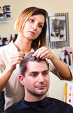 Happy female hairstylist setting client's hair Stock Image